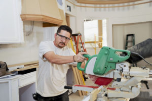 Carpenter uses a miter saw to cut molding for a custom kitchen remodel