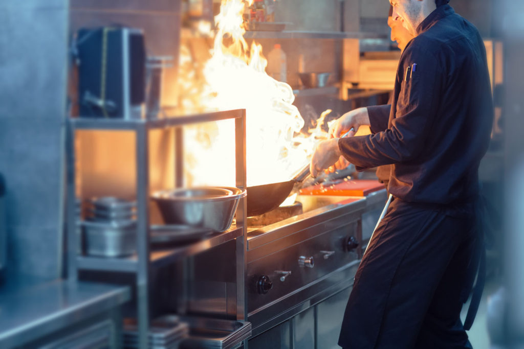 Chefs cooking over an open flame in a restaurant kitchen