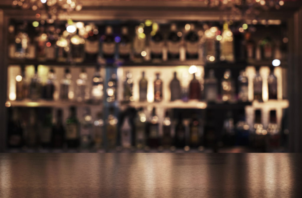 Close Up Of A Bar Counter With Defocused Bottles In The Background