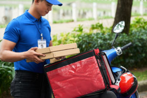 Pizza delivery driver holding pizza boxes next to his moped