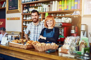 Male and female co-owners of a coffee shop stand together behind the counter